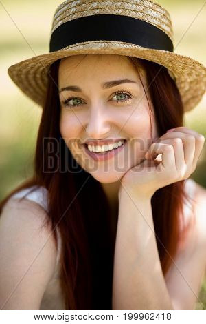 Portrait of young foxy lady in garden. Close up view of beautiful woman in straw hat, holding her hand close to chin.