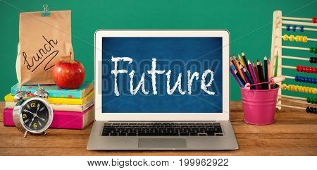 Future text against white background against school supplies with laptop on wooden table