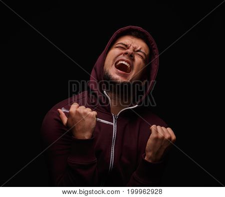 Portrait of a young male, suffering from pain, stress and drug addiction. A brunette guy in a red hoodie, holding a full syringe on a black background. Weakness, obsession, drug cravings concept.