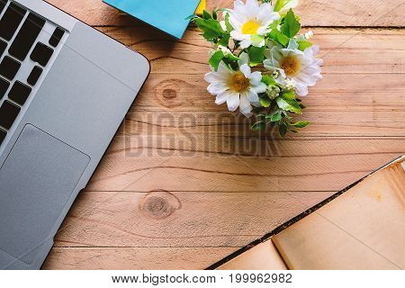Top view of computer laptop notepad book and flower on wooden table. Workspace Office.