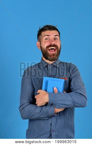 Textbook In Blue Color In Guys Hands On Blue Background
