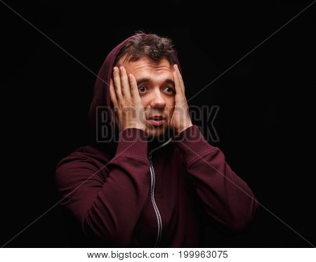 Shocked, surprised young man wearing a dark red hoodie on a black background. Sad, confused, lost student suffering with anxiety. Young people in need of treatment of mental issues and illness.