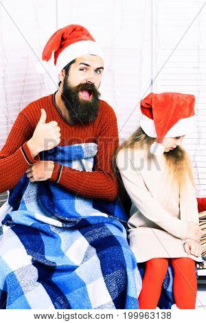 handsome bearded funny man with long beard in christmas red hat with blue checkered plaid and cute blonde offended girl in beige dress with crossed hands on white studio background
