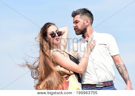 Sexy girl and guy with fashion face expressions hug each other. Man with beard and woman with messy long hair waving on wind. Couple carries packets on blue background. Relationship and love concept
