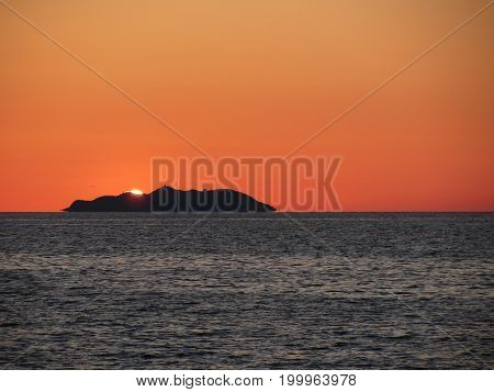 Beautiful sea sunset with island silhouette panorama . View of Gorgona island from Livorno city . Tuscany Italy