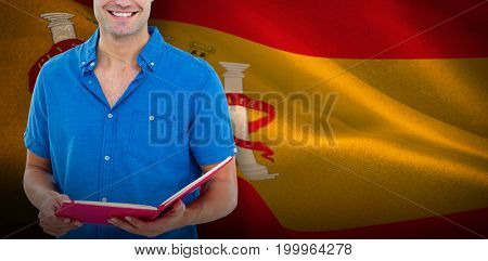 Happy student with notepad against digitally generated spanish national flag