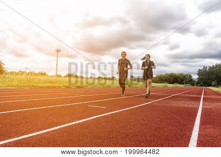 Two runners jogging on the race track Sport and Social activity concept