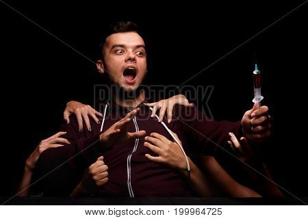 A guy in a dark black sweater holding a syringe on a black background. Many woman's hands touching an addicted young man, tearing him away from narcotics. Narcomaniac man suffering from drug cravings.