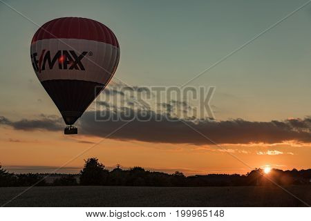 Saxon Germany - August 13 2017. Hot air balloon in sky and people in the basket fly over the landscape in Saxon. Germany