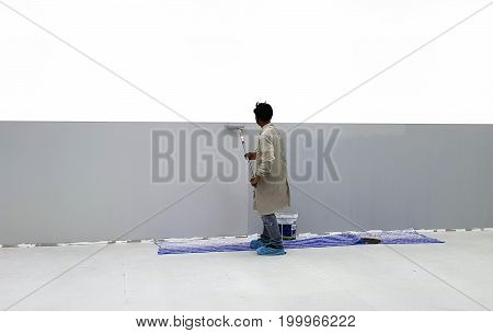 painter man at work with a paint roller isolated web banner wall painting concept