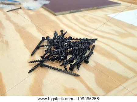 A pile of black self tapping screws isolated on wooden background.