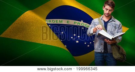 Student reading in library against digitally generated brazil national flag