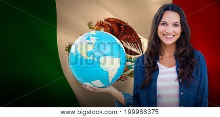 Happy woman with globe against digitally generated mexican national flag