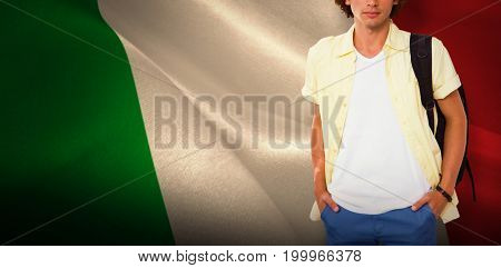 Casual young man in office corridor against digitally generated italian national flag