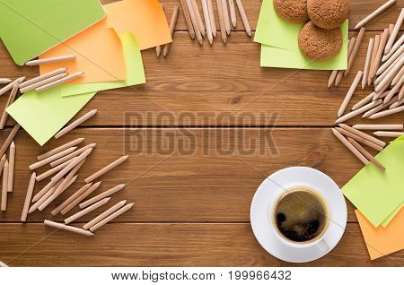 Top view on work space with stationery. Coffee break at office workplace. Assortment of pencils and colored memo stickers making frame for copy space on wooden table
