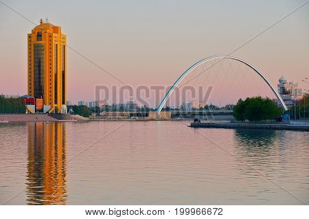 ASTANA, KAZAKHSTAN - SEPTEMBER 25, 2011: View to the city buildings and bridge over the Ishim river at dusk in Astana, Kazakhstan.