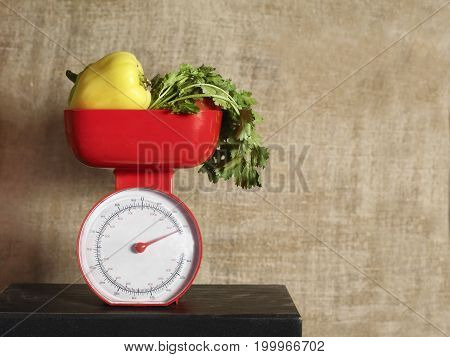 Front shot of food scale with bunch of fresh vegetables on a top, studio cropped photo