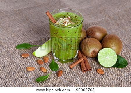 A view from above of a pile of juicy lime, sweet kiwi and apple on a light brown fabric background. Cinnamon sticks, almonds and green leaves on the table. Fruity cocktail full of nutritious vitamins.