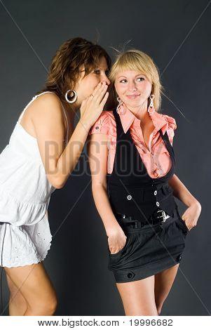 Girl Whispering in Friend`s Ear