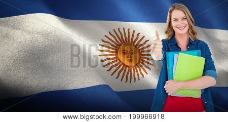 Smiling student holding notebook and file  against digitally generated argentinian national flag