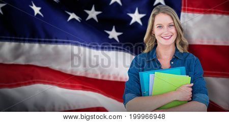 Smiling student holding notebook and file  against close-up of red and white american flag