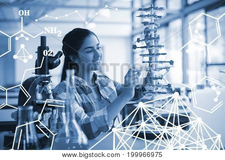 Kids doing a chemical experiment in laboratory against attentive schoolgirl experimenting molecule model in laboratory