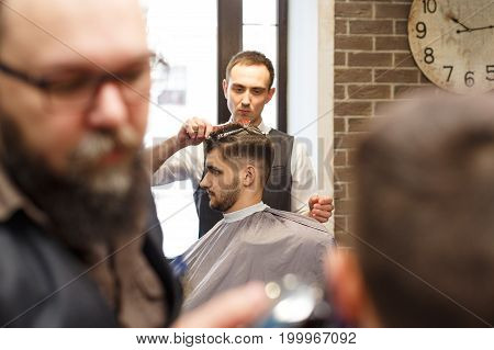 Barbers make haircut to clients at barbershop. Stylish hairdressers in male hair salon