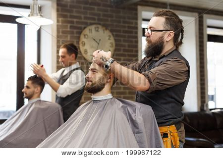 Barber make haircut with scissors at barbershop. Stylish hairdresser in male hair salon