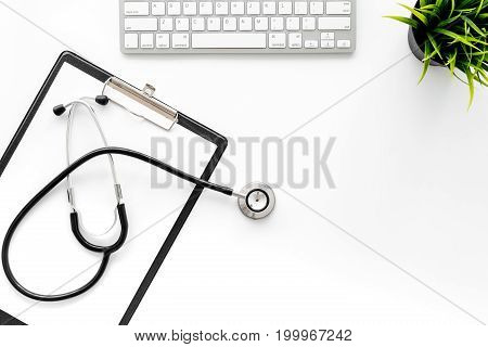 Doctor's workplace in clinic. Stethoscope and clip pad near keyboard top view.