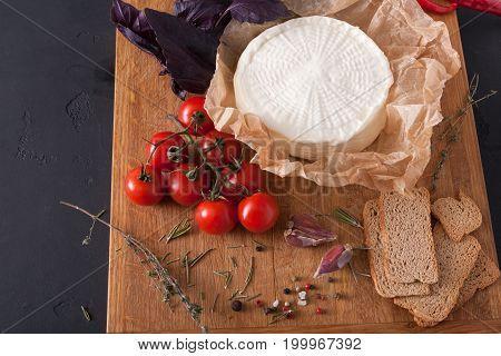 Cheese platter, homemade indian paneer cheese on wooden board with herbs, close-up