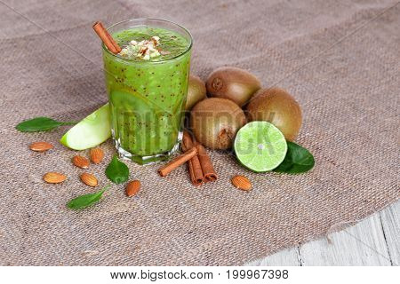 A view from above of a heap of a natural kiwi and lime cut in half on a light brown fabric on a gray wooden background. A healthful smoothie from tropical fruits and grated almonds on a table.