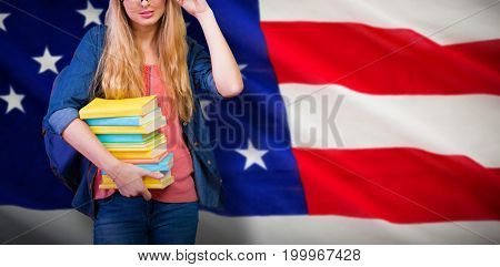 Pretty student in the library against close-up of us flag