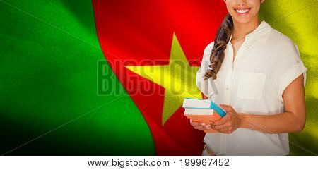Happy student against digitally generated cameroon national flag