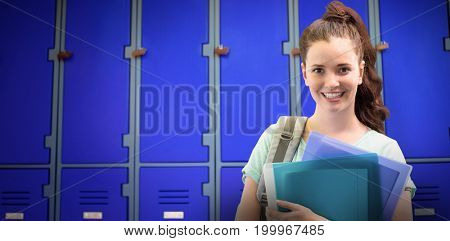 Smiling student against closed purple lockers in school