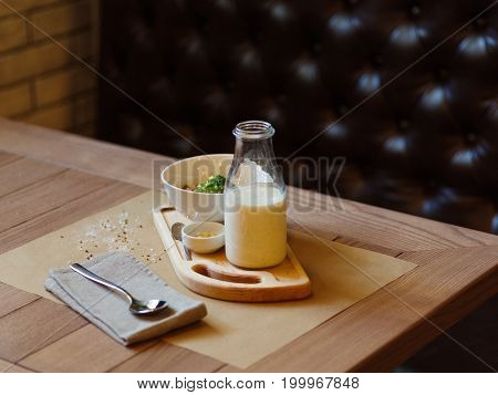 A close-up picture of beautiful lunch composition. A healthy salad with creamy sauce and a nutritious milkshake on a wooden table. A set of organic dishes and a spoon on a black background. Copy space