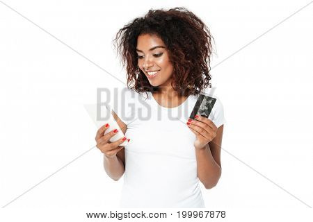 Picture of cheerful young african lady standing isolated over white background. Looking aside using mobile phone holding credit card.