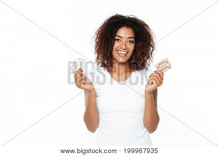 Image of smiling young african lady standing isolated over white background. Looking at camera holding pills.