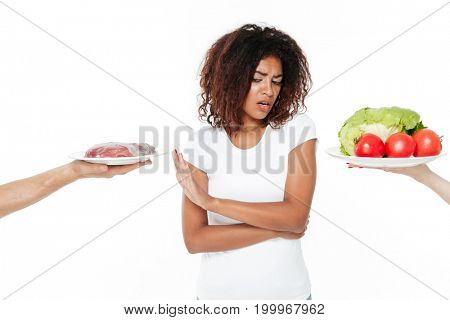 Picture of confused young african woman standing isolated over white background. Choosing between meat and vegetables.