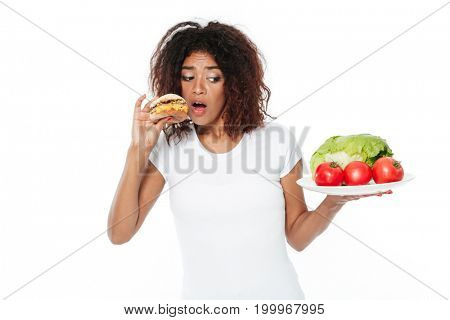 Picture of confused young african woman standing isolated over white background. Choosing between burger and vegetables.