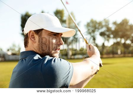 Close up of a young male golfer hitting a fairway shot at the green course