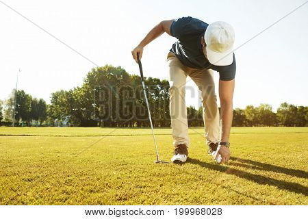 Young male golfer placing golf ball on a tee while playing on a green course