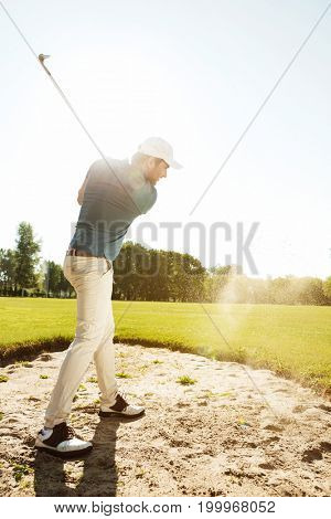 Male golfer hitting ball out of a sand trap while playing on a green course