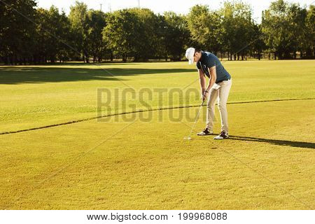 Male golfer putting golf ball on green while playing on a course