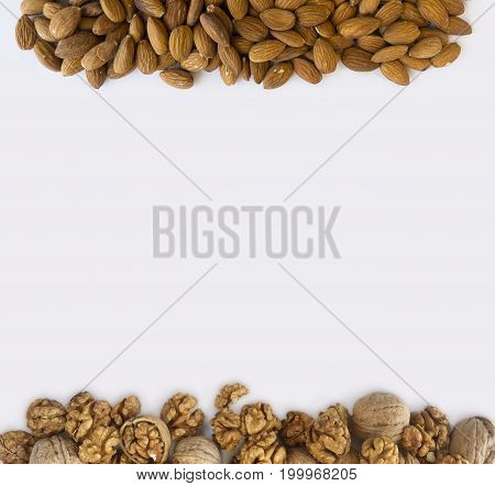 Almonds and walnuts at border of image with copy space for text. Background of nuts. Kernels walnuts and almonds on a white background. Top view. Vegetarian or healthy eating.