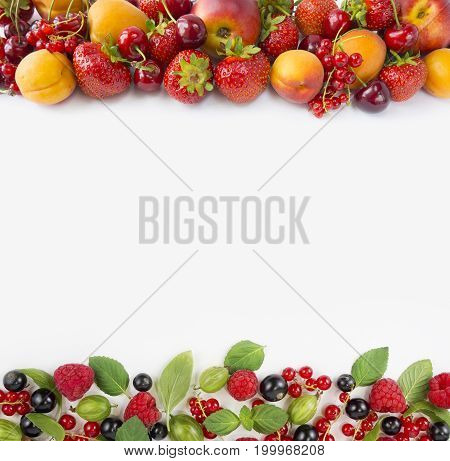 Various fresh summer berries. Ripe strawberries red currants apricots nectarines blackcurrants raspberries gooseberries and cherries on white background. Berries on white background. Top view. Berries at border of image with copy space for text