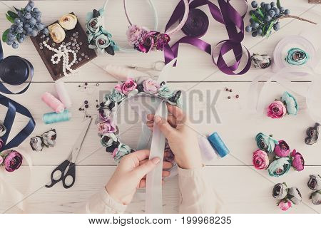 Master making handmade jewelry, top view. Needlewoman workplace with plastic beads, flowers and tools for creating accessories