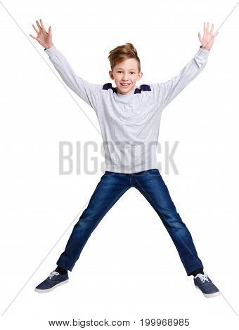 Laughing happy boy on white isolated background. Casual kid bouncing with raised hands at studio. Active life and happy childhood concept