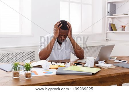 Stressed african-american employee in office. Upset while working on a new project