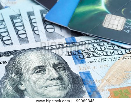 Close up view of credit plastic bank cards and american dollars banknotes. Financial operations shopping banking and money saving concept.