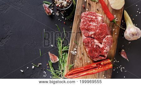 Raw rib eye steak with herbs and spices. Cooking ingredients for restaurant dish. Fresh meat, pepper salt, rosemary, chilli and garlic on wooden board at black background with copy space, top view